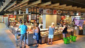 """Herzstück des Supermarktes ist ein Karrée aus mehreren Frischestationen - die """"offene Küche"""". Auch hier veredeln und verpacken die Mitarbeiter vor den Augen der Kunden die jeweiligen Produkte. Die Kacheloptik signalisiert Fachgeschäftscharakter."""