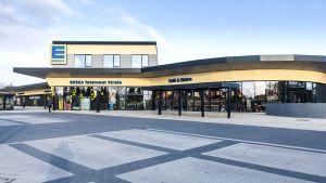 Seit Ende November 2016 ist der neueste Markt von Edeka-Händler Ingolf Schubert in Waren an der Müritz geöffnet. Nicht nur architektonisch bietet der sechste Standort mit 1.600 qm Verkaufsfläche Besonderes. Im Obergeschoss des Gebäudes befindet sich ein Verwaltungstrakt, an dem allerdings noch gebaut wird. Künftig sollen dort zehn der insgesamt 286 Mitarbeiter in zentralen Funktionen für die insgesamt sechs Edeka-Schubert-Märkte arbeiten. Die Gesamtinvestitionen am Standort belaufen sich auf 7,4 Mio. Euro.