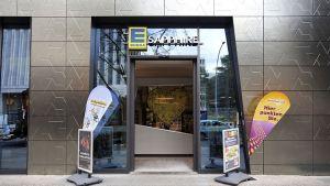"""Einzelhandel trifft Architektur - so lautet das Motto am neuen Standort von Edeka Minden-Hannover im Herzen von Berlin. Die rund 800 qm große Verkaufsfläche ist seit Januar 2017 im Erdgeschoss eines imposanten Neubaus von Star-Architekt Daniel Libeskind beheimatet. Die charakteristischen Ecken und Kanten des Gebäudes sollen an den Schliff eines Brillanten erinnern, weshalb Wohnhaus und Edeka-Markt den Namen """"Sapphire"""" tragen."""
