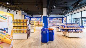 Mit den 19 bisherigen Werksverkaufsstellen des Keksherstellers hat das neue Outlet-Konzept wenig zu tun. Statt dem simplen Verkauf von B-Ware aus dem Karton kommt der Rostocker Standort eher als Markenstore daher. Mit viel Gelb und Blau, hellem Holzboden, moderner Markenpräsentation, großen Produktfotos und punktuellem Licht.
