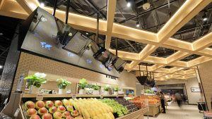 """JD.com hat seinen Vorzeigemarkt von """"7 Fresh"""" Ende 2017 in der Nähe der Pekinger Unternehmenszentrale eröffnet. Sein USP: starker Frischefokus, digitale Ladentechnik und die strategische Verknüpfung zu den eigenen Onlinediensten. Zudem ist der Laden mit viel Retailtechnik ausgestattet. Die gläsernen Monitore, sogenannte """"Magic Mirrors"""" etwa über den Obst- und Gemüseständen, ähneln den interaktiven Regalen des Futurestores von Coop Italia bei Mailand. Sobald ein Produkt aus dem Warenträger entnommen wird, zeigen sie Zusatzinformationen zu Herkunft oder Nährstoffgehalt an."""