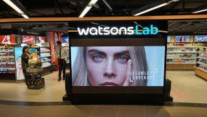 """In Hongkong testet AS Watson einen Drogeriemarkt, der in die Zukunft weisen soll. Das """"Watsons Lab"""" ist ein unbemannter Store mit jeder Menge Technik – auch wenn jetzt noch eine Mitarbeiterin den Kunden die Neuheiten erklärt."""