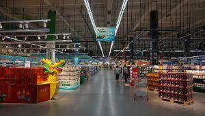 Das Ladendesign im ersten Teil des Marktes erinnert an ein weitläufiges europäisches SB-Warenhaus. Die Regale sind auf 1,50 Meter abgesenkt. Von der hohen Decke hängen weiße und schwarze Leuchten, die den Raum in akzentuiertes Licht tauchen.