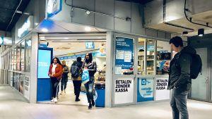 """In der U-Bahnebene des Amsterdamer Bahnhofs testet Ahold Delhaize in einer Filiale von AH to go das kassenlose Bezahlsystem """"Tap to go"""". """"Bezahlen ohne Kasse"""" steht auf großen Schildern an der Fassade."""