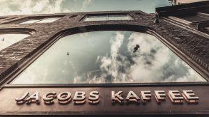 """Im """"Johann Jacobs Haus"""" dreht sich über fünf Stockwerke alles um die braune Bohne. Nach dem Abriss des Vorgängergebäudes und einer zweijährigen Bauphase eröffnete Johann Christian Jacobs, der Urgroßneffe des Gründers, im Juli 2020 das neue Gebäude. Es steht an der Stelle des ehemaligen Stammsitzes des Kaffeeunternehmens Jacobs in der Obernstraße 20, einer der zentralen Fußgängerzonen der Hansestadt."""