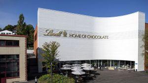 """Trotz Onlineboom und Corona-Krise setzen viele große Konsumgüterhersteller nach wie vor auf stationäres Marketing, um die Verbraucher für ihre Marken zu begeistern. Vor allem, wenn es ihnen gelingt, eine emotional aufgeladene Atmosphäre zu kreieren, die alle Sinne anspricht. Wie im neuen """"Home of Chocolate"""", das Schokoprimus Lindt & Sprüngli im Herbst 2020 am Unternehmenssitz Kilchberg bei Zürich eröffnet hat."""