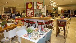 Kundinnen der Galeria Kaufhof am Berliner Alexanderplatz können jetzt beim Shoppen eine Pause machen, ohne die Etage zu verlassen. Ende September eröffnete die Kaufhof-Tochter Dinea mitten in der Abteilung für Damenmode auf der 1. Etage ein Bistro-Café.
