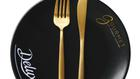 xxx Beautiful gold cutlery - fork and knife on black plate on black background. Top View, above. Ho
